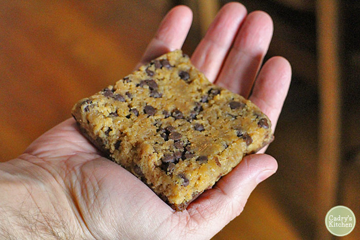 Hand holding chocolate chip cookie bar.