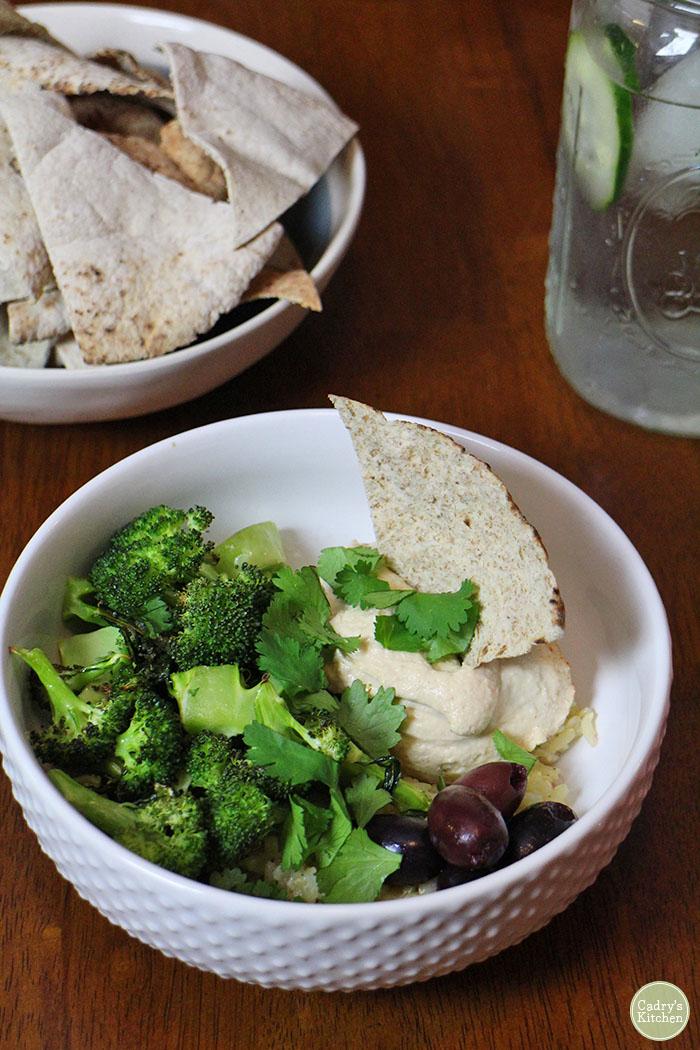 Hummus bowl with broccoli, pita, and kalamata olives.