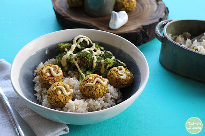 Falafel in bowl with broccoli and rice, drizzled with peanut sauce.
