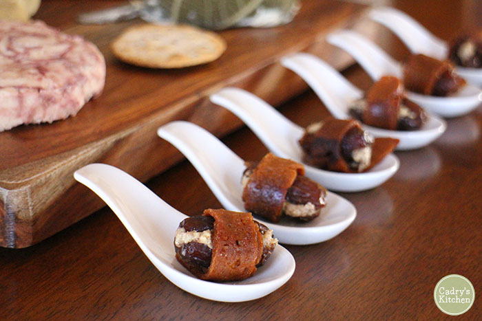 Seitan bacon wrapped dates with almond butter on little ceramic spoons.