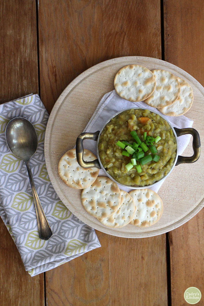 Split pea soup in pot with spoon and napkin.