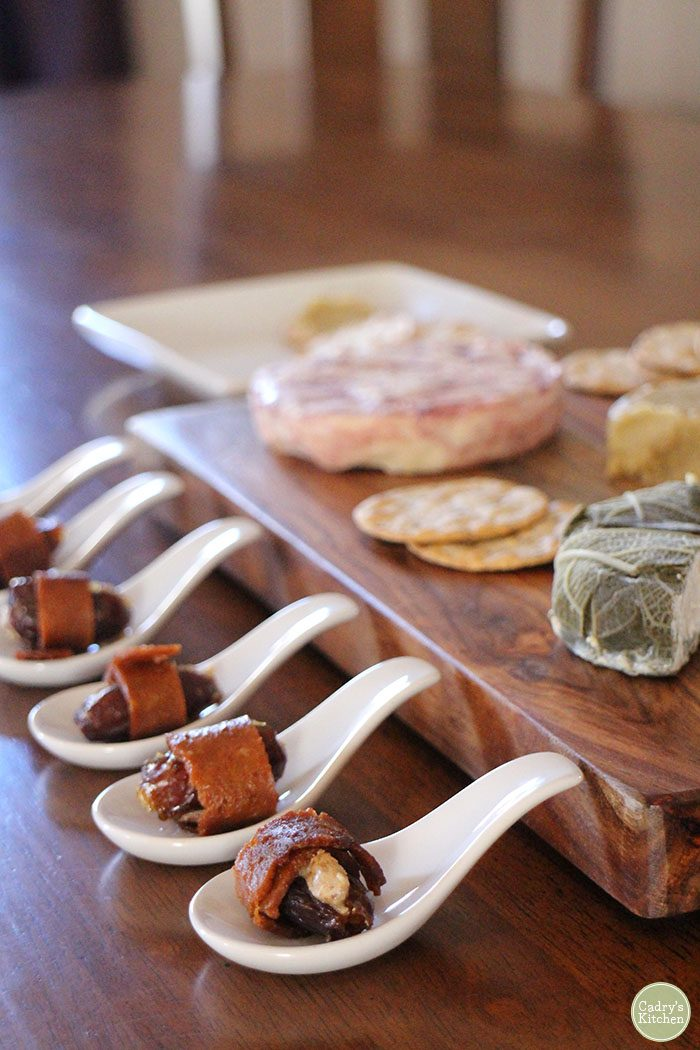 Seitan bacon wrapped dates with almond butter by charcuterie board with non-dairy cheese.