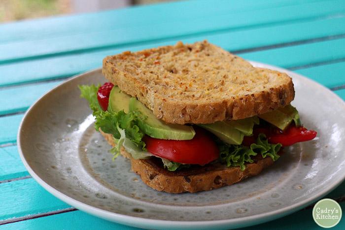 Seitan bacon, lettuce, tomato, and avocado sandwich on plate.