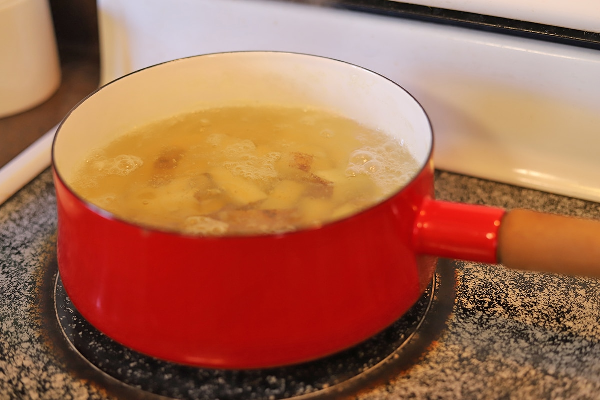 Potatoes in pot of water on stove.
