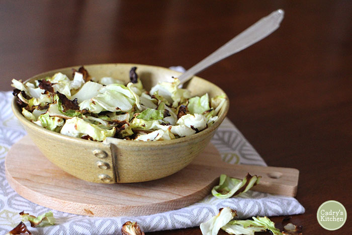 Vegan cabbage recipe. Crispy cabbage in a bowl with spoon.