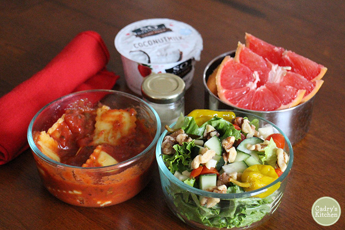 Salad, ravioli, grapefruit, and dressing in reusable containers. Coconut milk and silverware in cloth napkin.