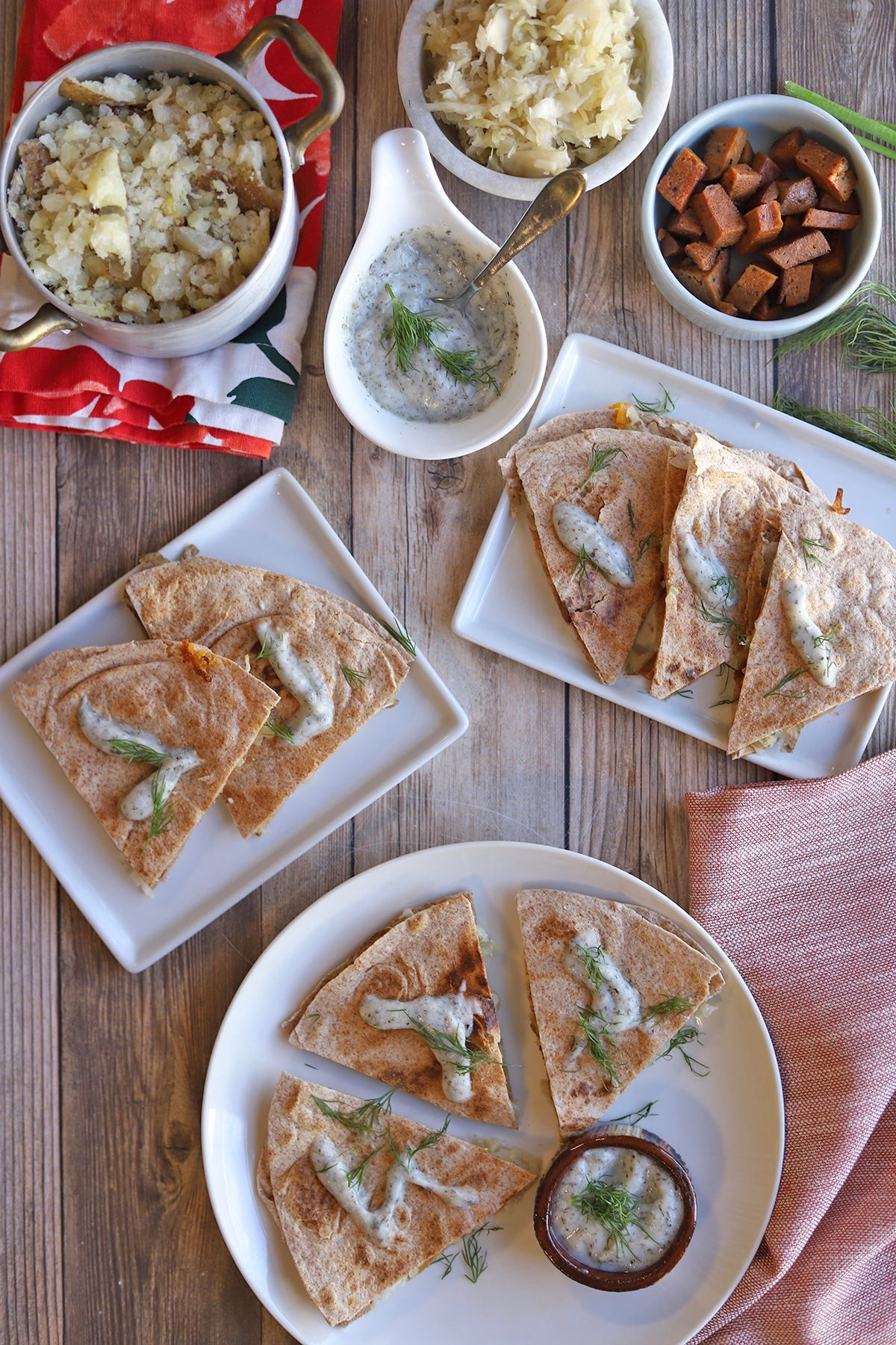 Overhead quesadillas on plates with potatoes and yogurt ranch sauce.