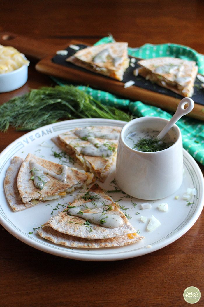 Vegan appetizer recipes. Pierogi quesadillas - All of the flavors you love in a pierogi in quesadilla form. This vegan recipe includes tortillas packed with potatoes, sauteed onions, sauerkraut, and non-dairy cheese with a yogurt ranch sauce. | cadryskitchen.com