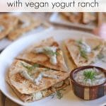 Text overlay: Pierogi quesadillas with vegan yogurt ranch. Toasted tortilla wedges stuffed with potatoes on plate by yogurt sauce.