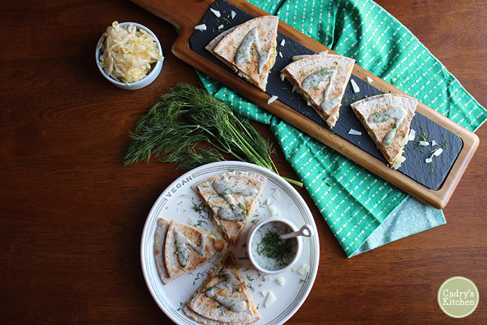 Overhead vegan quesadilla on plate with pierogi quesadillas on platter.