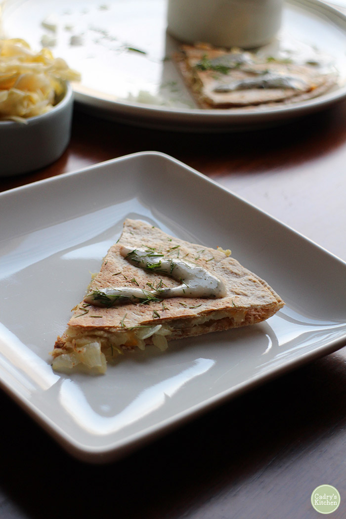 Pierogi style vegan quesadilla triangle on plate and drizzled with non-dairy yogurt ranch.