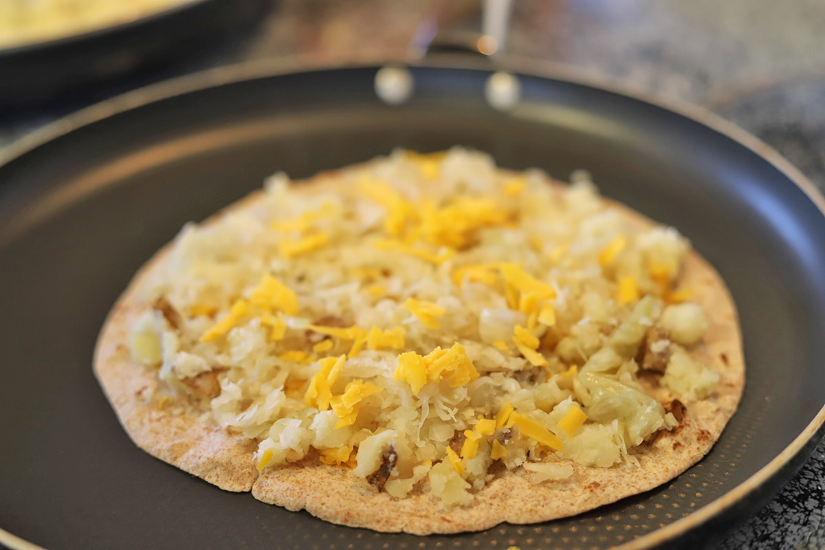Tortilla in skillet with potatoes, shredded vegan cheese, and sauerkraut.