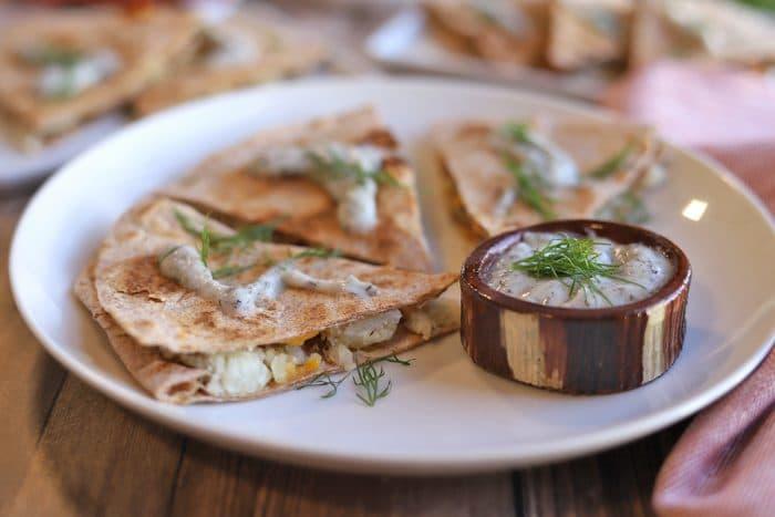 Pierogi quesadilla wedges on plate with yogurt ranch sauce.