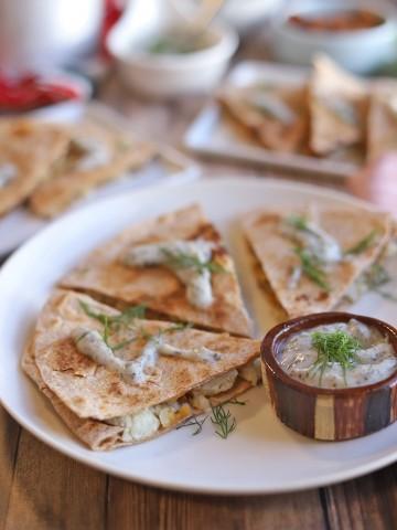 Vegan quesadillas stuffed with potatoes, sauerkraut, and non-dairy cheese on plate with yogurt sauce.