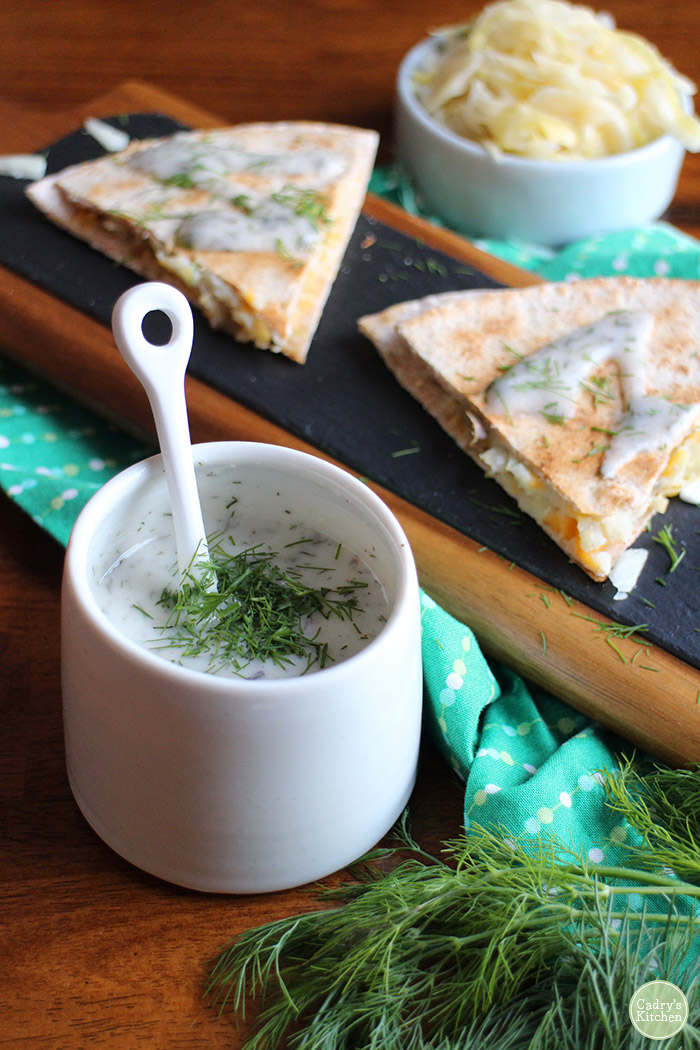 Non-dairy yogurt ranch in cup topped with fresh dill. Next to vegan quesadilla on platter.