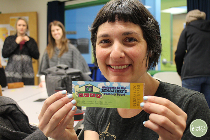 Close-up Becky Striepe holding ticket for Ben & Jerry's factory tour.