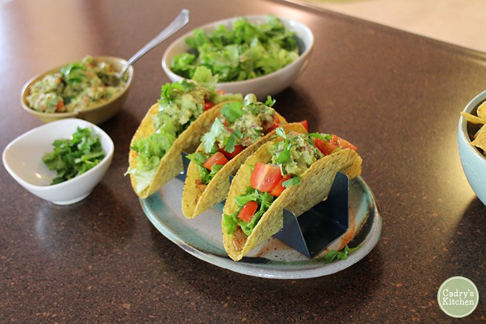 Tacos in holders by guacamole and lettuce.