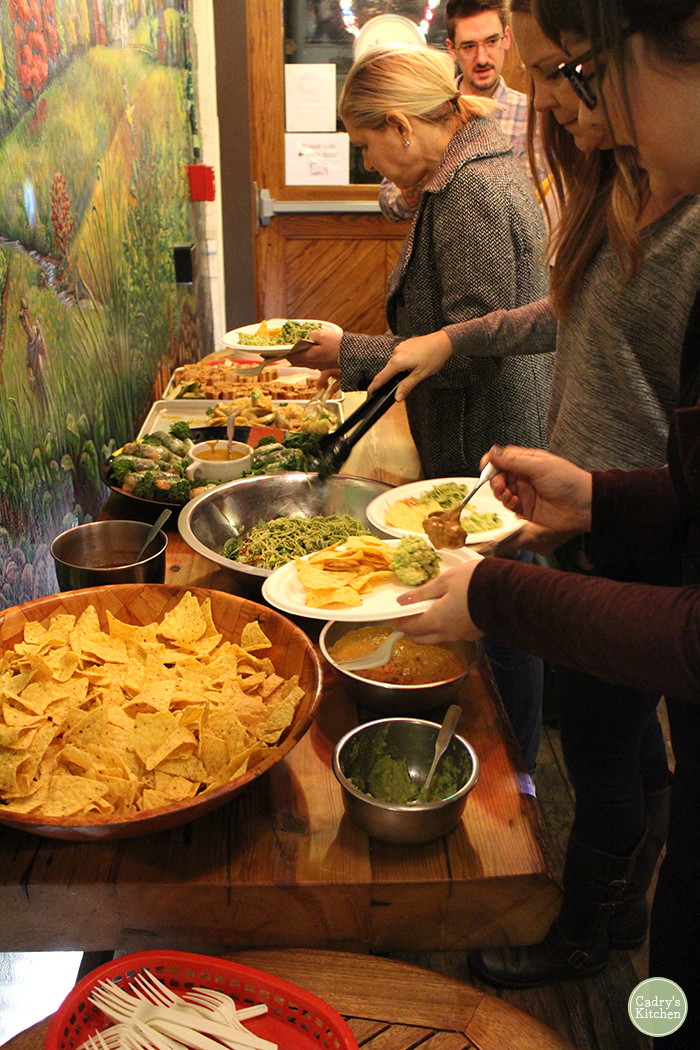 People scooping food onto plates at Pingala vegan restaurant.