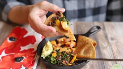 Hand holding fried tortilla wedge topped with sweet potato, kale, and beans.