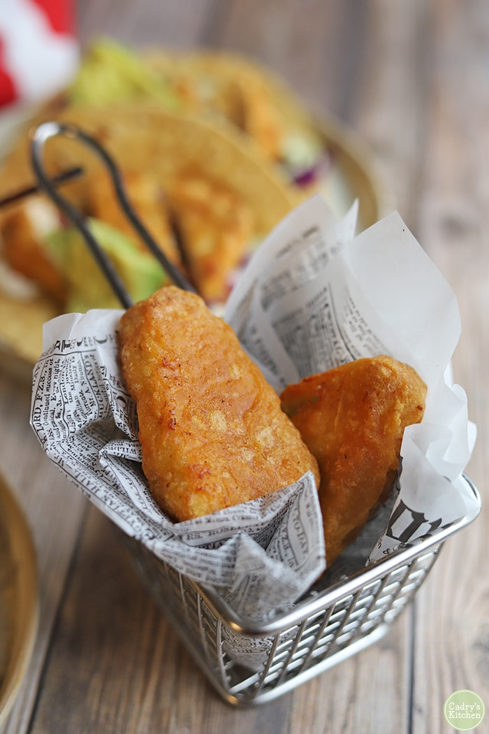 Gardein fishless filets in newspaper in metal fry basket.