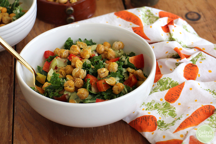 Kale salad in bowl with roasted chickpeas and creamy cashew dressing.