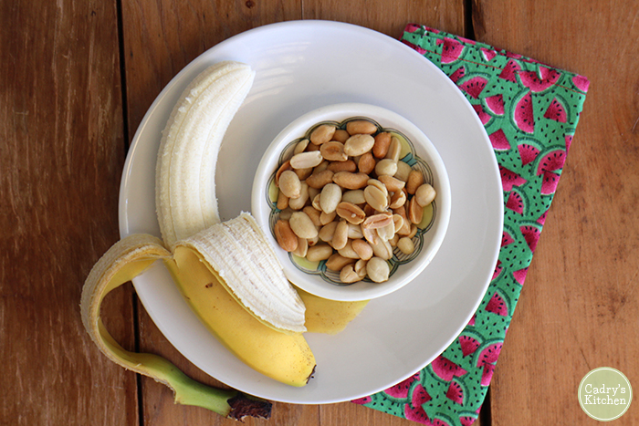 Banana with bowl of peanuts on plate.