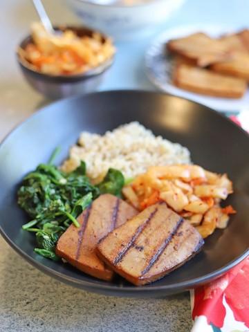 Vegan bulgogi tofu bowl with sauteed spinach, brown rice, and kimchi.