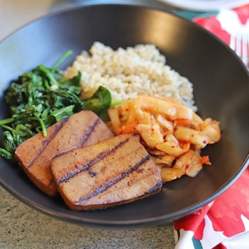 Grilled slabs of bulgogi tofu in bowl with kimchi, sauteed spinach, and brown rice.