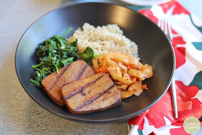 Grilled slabs of tofu in bowl with kimchi, sauteed spinach, and brown rice.