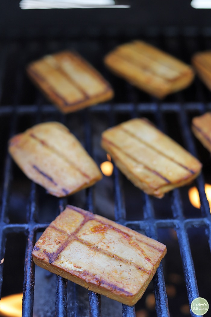 Slices of bulgogi tofu on outdoor grill.