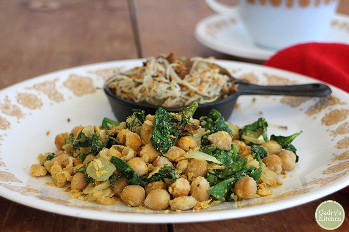 Chickpea scramble with spinach on plate with hash browns in mini skillet.