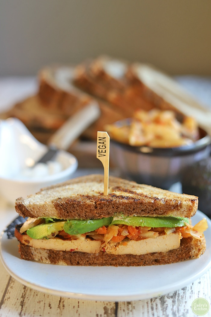 Close-up of sliced sandwich with tofu, kimchi, and avocado on rye bread.