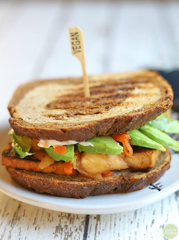 Close-up of sandwich with rye bread, bulgogi tofu, avocado, and kimchi.