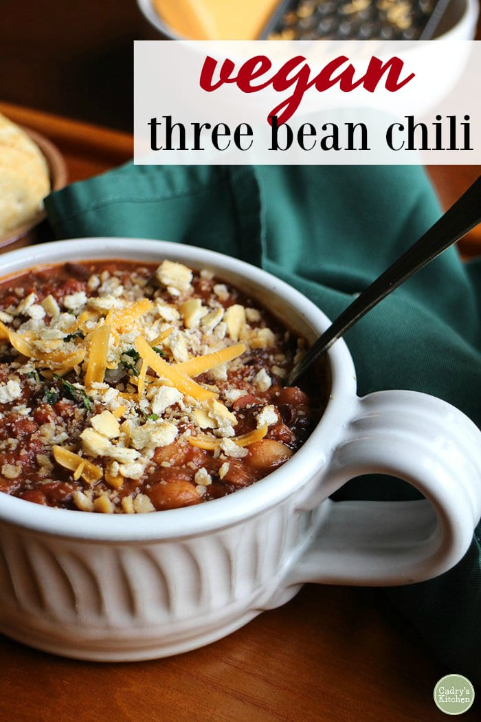 Vegan three bean chili text + bowl of chili with crackers and non-dairy cheese.