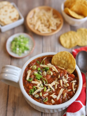 Tortilla chip in bowl of 3 bean chili.