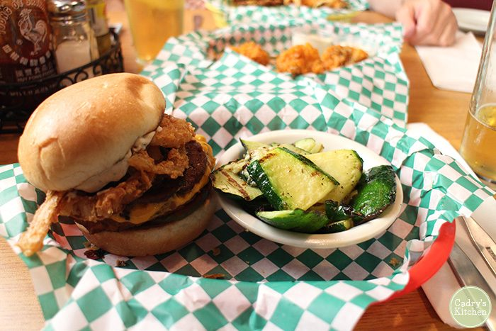 Cowboy burger in basket with grilled zucchini cup.