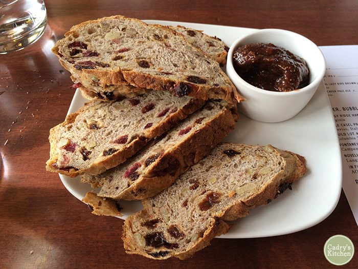 Slices of cranberry walnut bread on plate with fig spread at Living Kitchen.