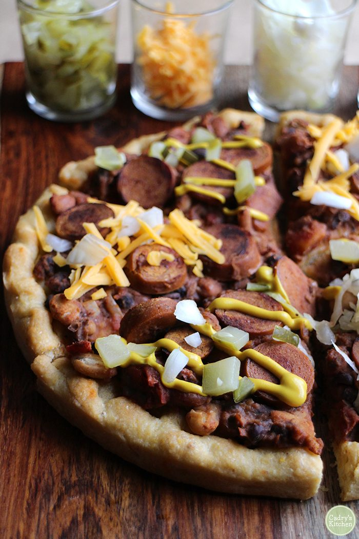 Close up picture of vegan chili dog pizza topped with mustard, pickles, and onions on a wood board.