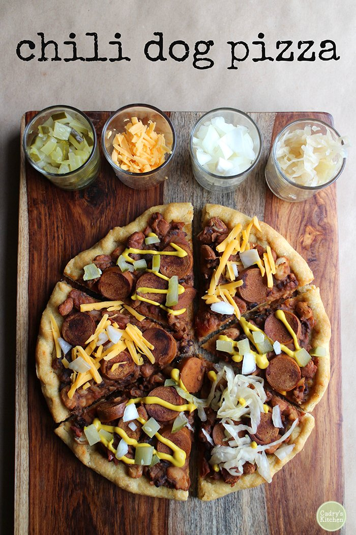 Vegan chili dog pizza on wood cutting board with toppings.