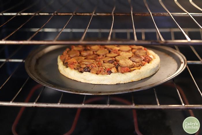Vegan chili dog pizza in oven.