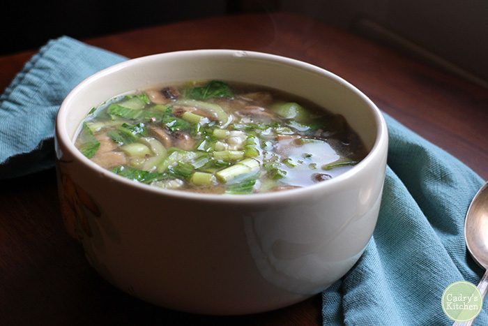 Vegan miso soup in bowl with blue napkin and spoon.