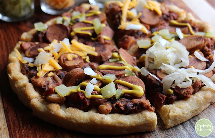 Close up of vegan chili dog pizza topped with 3 bean chili, a veggie dog, and mustard, pickles, and onions.