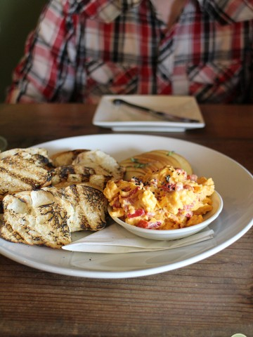 Pimento cheese in bowl by grilled bread.