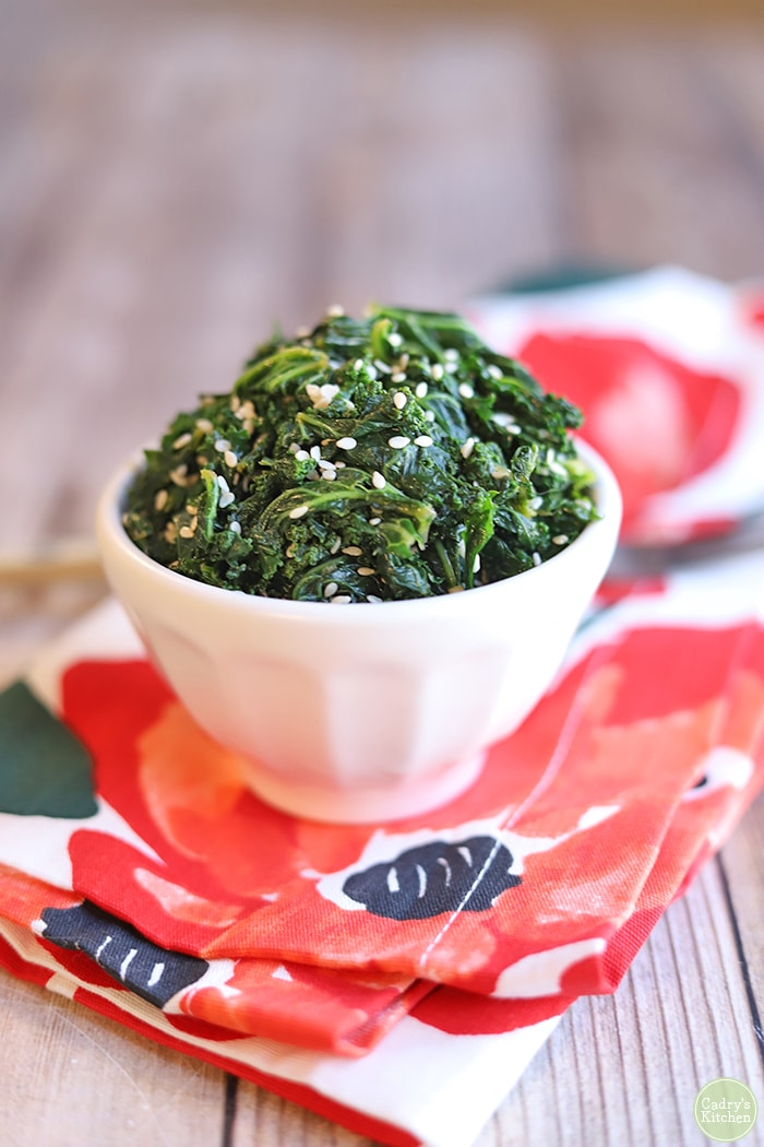 Steamed kale with sesame seeds on flowered napkin.