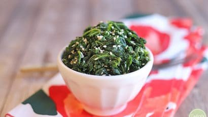 Sesame kale with garlic in cup on flowered napkin.
