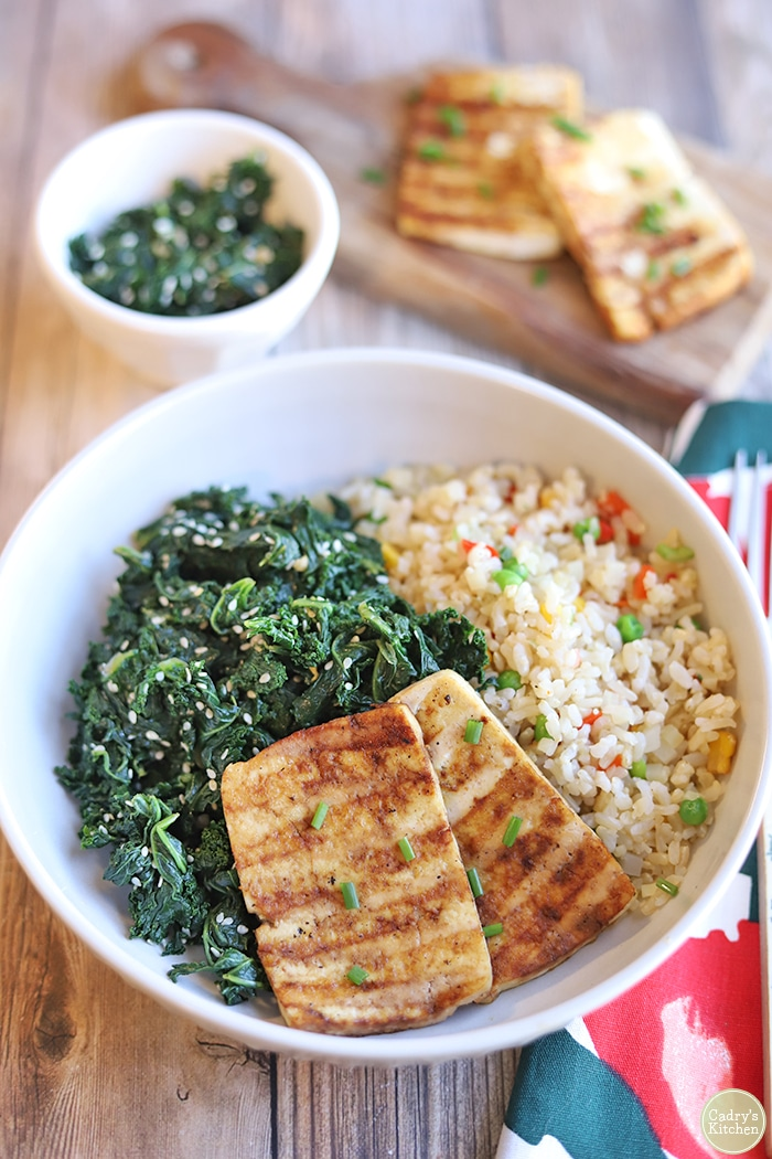 Grilled tofu, dark leafy greens, and rice in bowl by napkin.