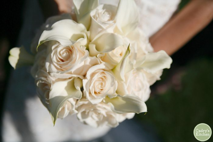 Bride holding bouquet of roses and calla lilies.
