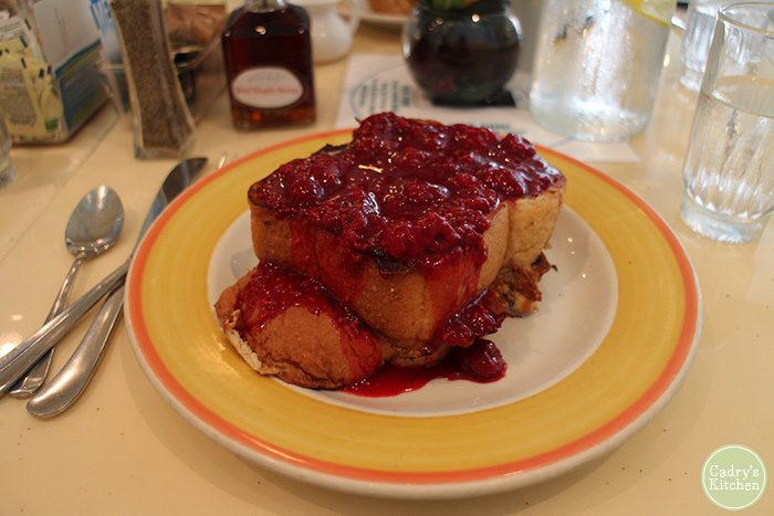 French toast with raspberry puree on yellow plate.