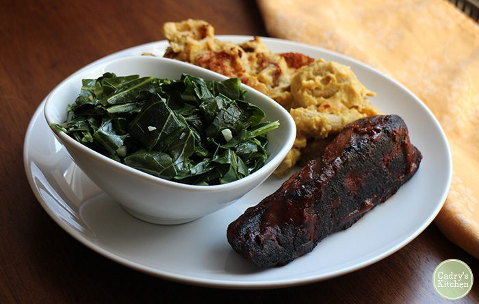 Seitan ribs on plate with mac & cheese and collard greens.