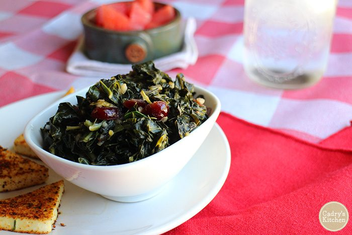Smoky sweet vegan collard greens in bowl. Checkered table cloth & red napkin on table.
